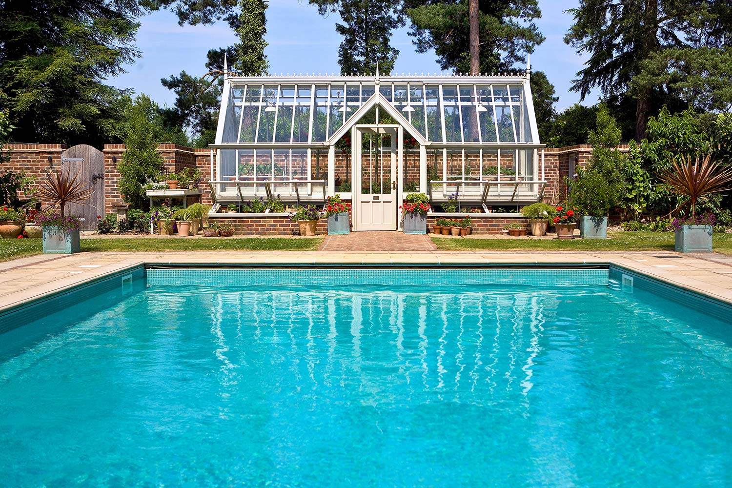 A poolside location for this half-span lean-to greenhouse with a double lobby in Off-white (Alitex)