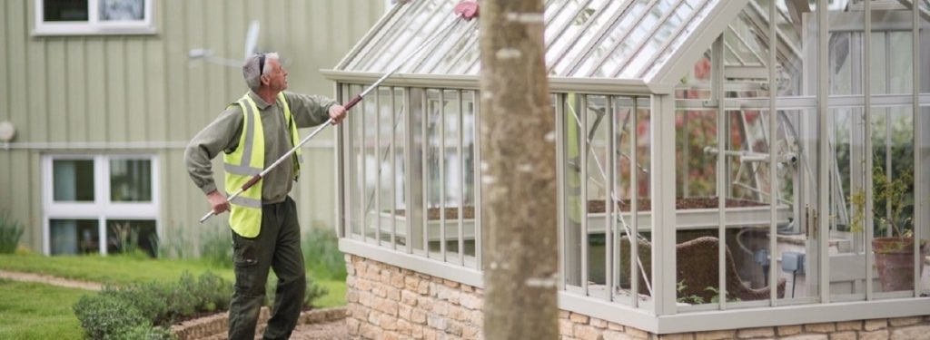 image showing a man cleaning a greenhouse